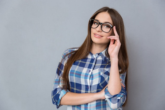 Ritratto di una ragazza intelligente hipster piuttosto sorridente in camicia a quadri con capelli lunghi con gli occhiali