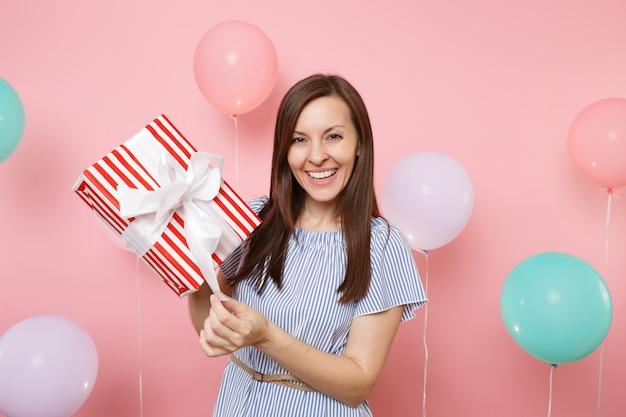 Ritratto di donna abbastanza sorridente in abito blu che slega l'arco sulla scatola rossa con regalo presente su sfondo rosa pastello con mongolfiere colorate. festa di compleanno, concetto di emozioni sincere della gente.