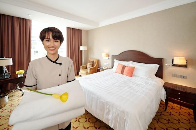 Ritratto di giovane cameriera vietnamita abbastanza sorridente in piedi in una camera d'albergo con una pila di asciugamani e un bellissimo fiore di calla