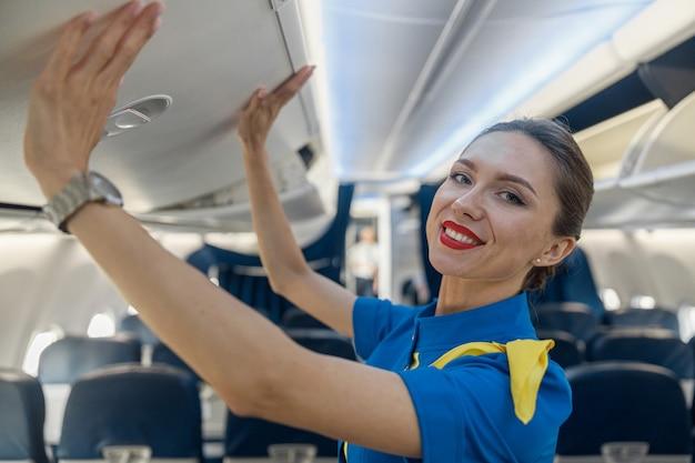 Ritratto di bella hostess in uniforme blu che sorride alla macchina fotografica mentre chiude il vano bagagli a mano, rimanendo sul corridoio all'interno dell'aereo. trasporto, concetto di occupazione