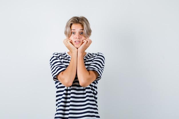 Ritratto di un bel ragazzo adolescente che si fa il cuscino sulle mani con una maglietta a righe e sembra spaventato vista frontale