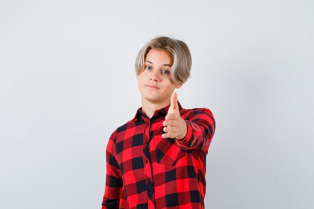 Ritratto di un bel ragazzo adolescente che allunga la mano davanti con una camicia a quadri e sembra fiducioso in vista frontale