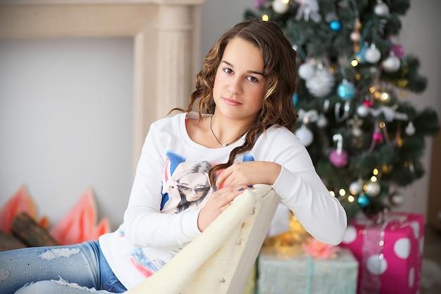 Ritratto di una bella ragazza adolescente con capelli lunghi fluenti in interni con decorazioni natalizie