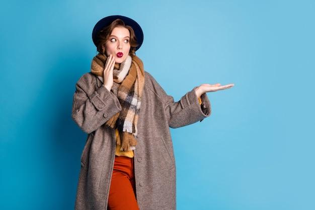 Ritratto di signora graziosa del viaggiatore che tiene il nuovo prodotto sul braccio aperto offre i prezzi finali bassi della stagione indossa il cappello dei pantaloni della sciarpa del cappotto grigio casual elegante.
