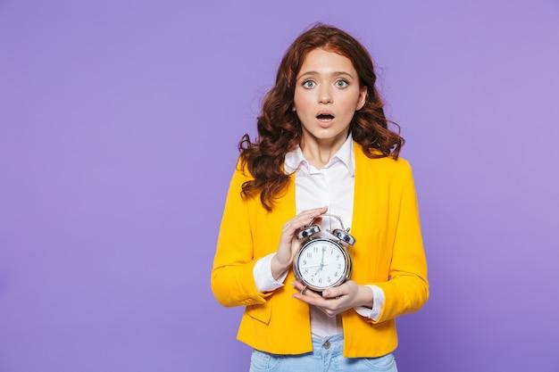 Ritratto di una giovane donna dai capelli rossi piuttosto sconvolta in piedi su viola, tenendo sveglia