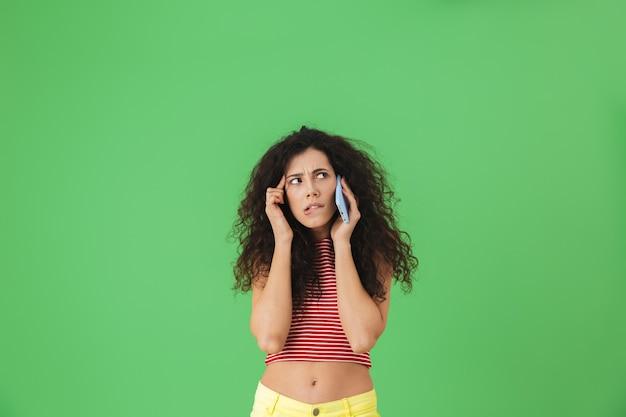 Ritratto di una bella donna di 20 anni vestita in modo casual mentre parla al telefono cellulare isolato su verde