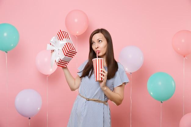 Ritratto di bella donna in abito blu che guarda in alto tenendo in mano una scatola rossa con regalo regalo bevendo soda o cola da un bicchiere di plastica su sfondo rosa pastello con mongolfiere colorate. festa di compleanno.