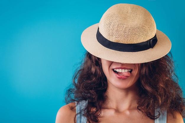 Ritratto di una bella donna che si nasconde sotto il cappello e mostra la lingua su sfondo blu