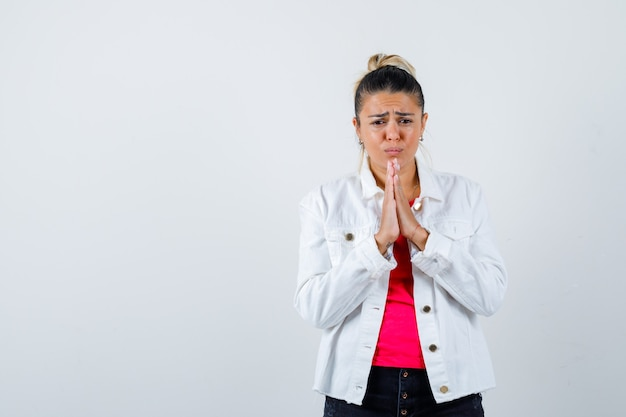 Ritratto di donna graziosa mantenendo le mani nel gesto di preghiera in giacca bianca e guardando triste vista frontale