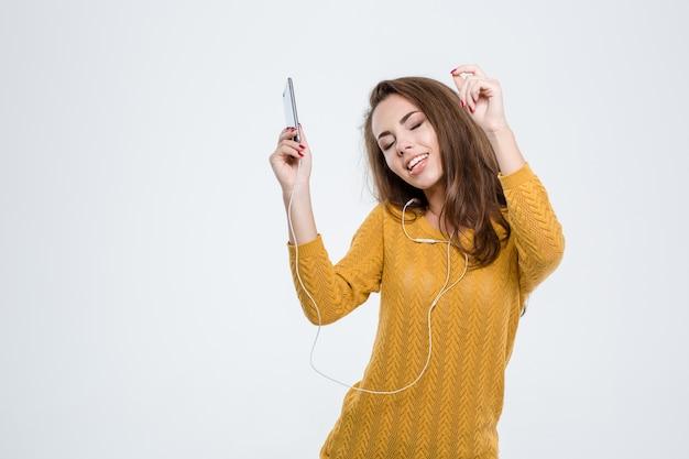 Ritratto di una bella donna che ascolta musica in cuffia isolata su uno sfondo bianco