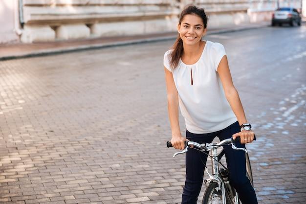 Ritratto di una bella donna in bicicletta per la strada della città e guardando la parte anteriore