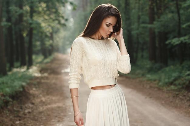 Ritratto di una bella donna in un maglione bianco sulla strada nella foresta con nebbia