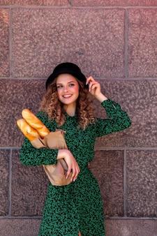 Ritratto di donna graziosa con baguette in mano sulla trama di sfondo della parete. la ragazza vestita in stile francese mostra emozione. femmina in vestiti alla moda che tengono baguette fresche. posto per iscrizione o logo
