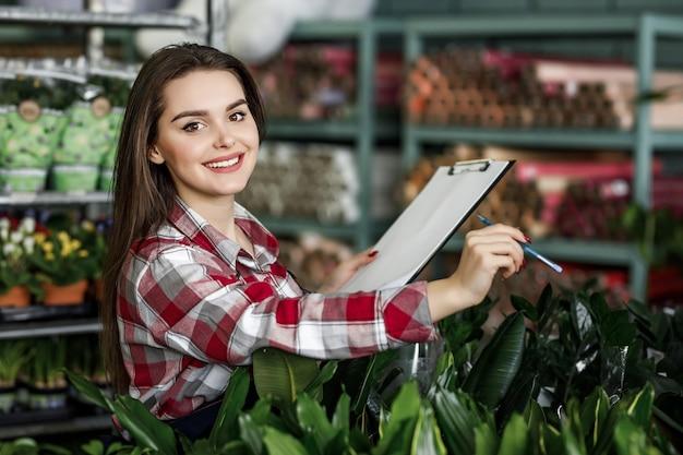 Ritratto di una bella donna che lavora nella serra del centro giardino con cartella e piante di controllo