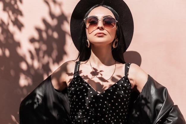 Ritratto piuttosto giovane donna chic in cappello elegante in abito di moda in giacca di pelle vintage in occhiali da sole sulla parete di sfondo rosa sulla spiaggia assolata. la ragazza attraente in vestiti estivi gode dell'umore