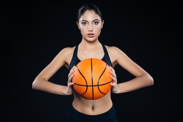 Ritratto di una giovane donna di forma fisica che tiene e posa con una palla da basket su sfondo nero