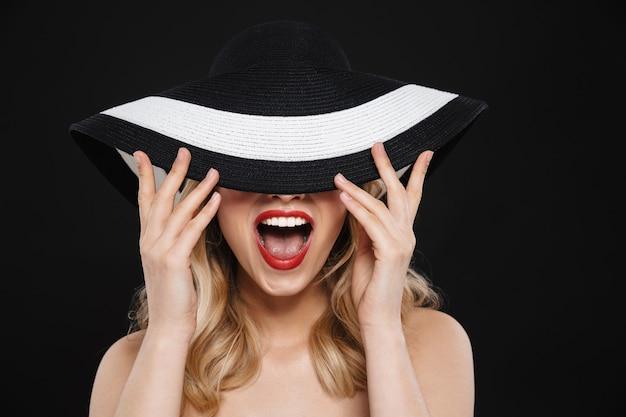 Ritratto di una donna bionda emozionante felice abbastanza giovane con le labbra rosse di trucco luminoso che posano il cappello d'uso isolato.