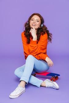 Ritratto di una donna dai capelli rossi piuttosto giovane seduto su skateboard su viola, ascoltando musica con le cuffie
