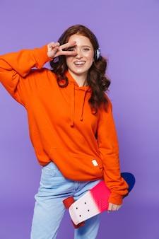 Ritratto di una bella giovane donna dai capelli rossi in piedi su viola, tenendo lo skateboard, ascoltando musica con le cuffie