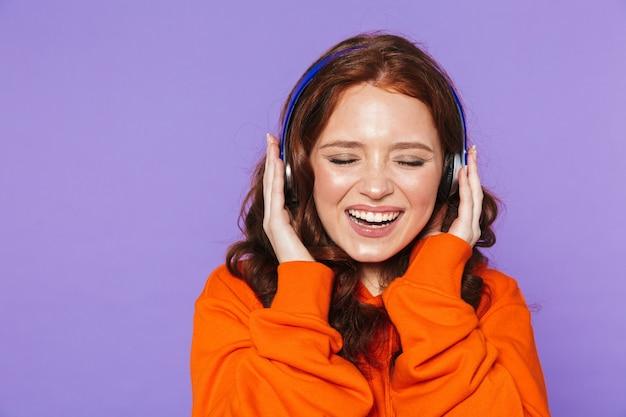 Ritratto di una bella giovane donna dai capelli rossi in piedi su viola, ascoltando musica con le cuffie