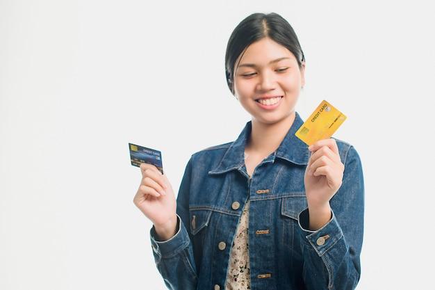 Il ritratto di una giovane donna graziosa si è vestito in carta di credito della tenuta della camicia del denim al suo fronte isolata sopra la parete bianca