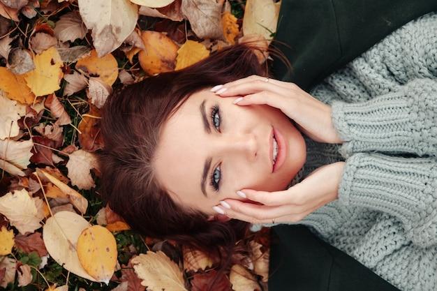 Ritratto di una bella giovane donna di aspetto slavo in abbigliamento casual in autunno, sdraiata su foglie gialle autunnali. modello carino passeggiate nel parco in autunno dorato sullo sfondo della natura. copia spazio