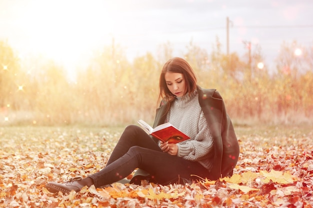 Ritratto di bella giovane donna di aspetto slava in abbigliamento casual in autunno, leggendo un libro in radura. modello carino che cammina nel parco in autunno dorato sullo sfondo della natura. copia spazio