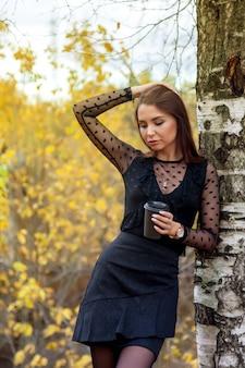Ritratto di bella giovane donna di aspetto slavo in abito scuro e un bicchiere di caffè in autunno, in piedi accanto alla betulla sullo sfondo di un autunno parco e stagno con acqua