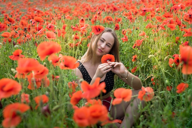 Ritratto di una donna abbastanza giovane in abiti sportivi che si siede nel campo di papaveri fioriti