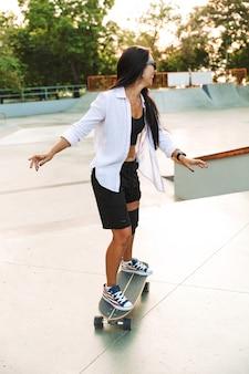 Ritratto di una bella giovane donna in streetwear che sorride mentre cavalca lo skateboard in skate park