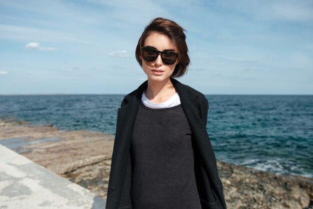 Ritratto di donna abbastanza giovane in occhiali da sole e giacca nera in riva al mare in autunno