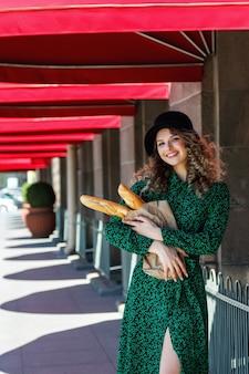 Ritratto piuttosto giovane donna con baguette in mano sulla strada. la ragazza vestita in stile francese mostra emozione. giorno soleggiato. femmina in vestiti alla moda che tengono baguette fresche. copia spazio