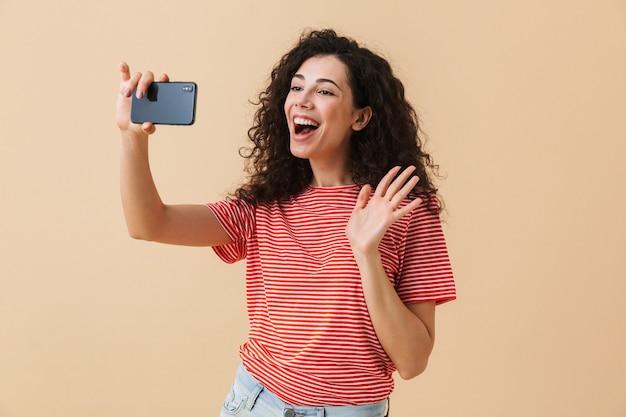 Ritratto di una bella giovane donna con i capelli ricci prendendo selfie