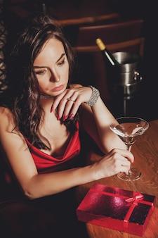 Ritratto piuttosto giovane donna con confezione regalo nel ristorante notturno. donna triste a causa del regalo. concetto di celebrare il giorno di san valentino in un ambiente intimo. regalo romantico per la tua amata. copia spazio