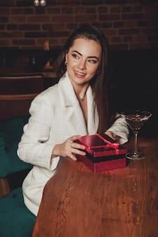 Ritratto piuttosto giovane donna con confezione regalo nel ristorante notturno. regalo di apertura sorridente femminile. concetto di celebrare il giorno di san valentino in un ambiente intimo. regalo romantico per la tua amata. copia spazio