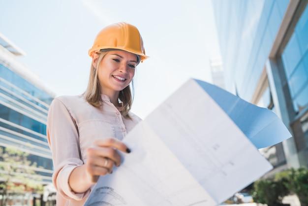 Ritratto di architetto professionista che indossa il casco giallo e guardando le stampe blu all'esterno di un edificio moderno. concetto di ingegnere e architetto.