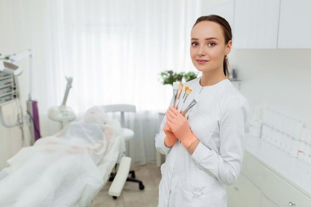 Ritratto di un estetista professionista con spazzole in mano. bella donna caucasica su una procedura di cosmetologia.