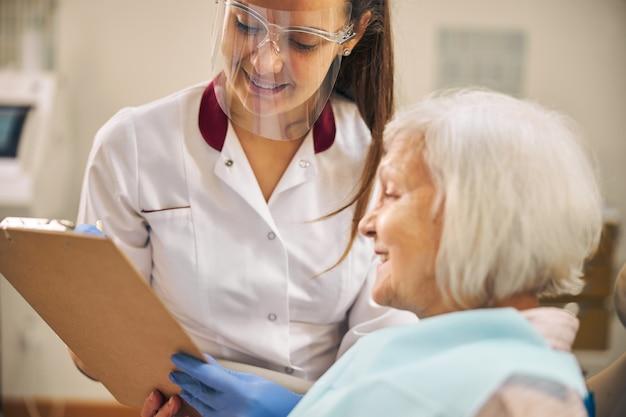 Ritratto di una dottoressa professionista allegra in maschera protettiva che parla con la sua cliente femminile nella sua clinica