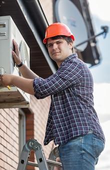 Ritratto di elettricista professionista che ripara il condizionatore d'aria sulla parete esterna dell'edificio