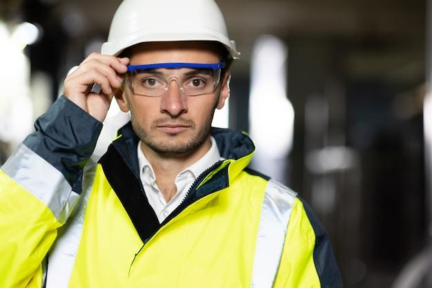 Ritratto di ingegnere professionista o lavoratore che indossa l'uniforme di sicurezza e l'operatore ecologico dell'elmetto protettivo