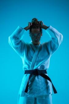 Ritratto di judoista professionista femminile isolato su sfondo blu studio in neon