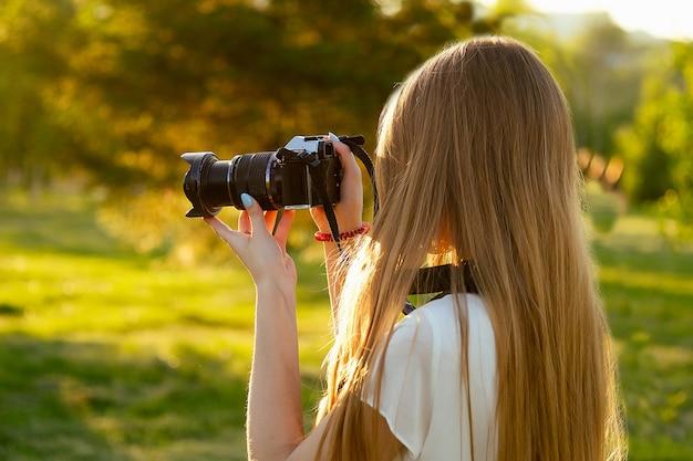 Ritratto di fotografa professionista nel parco che fotografa su una macchina fotografica. servizio fotografico sessione fotografica nella vista posteriore della città.