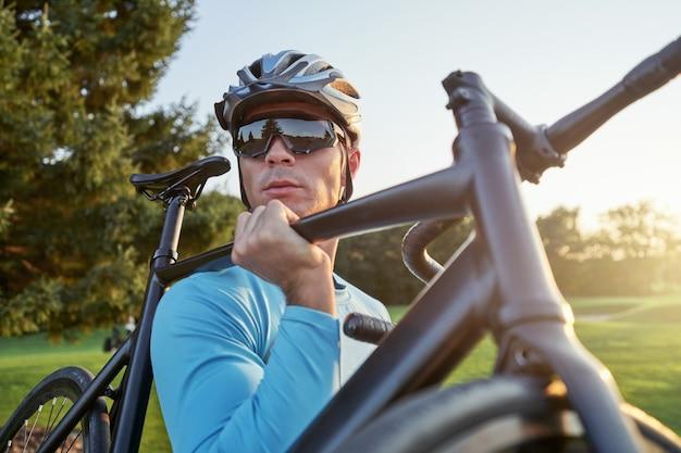 Ritratto di ciclista professionista maschio che indossa abbigliamento sportivo e casco protettivo che porta la sua bici