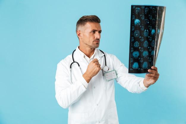Ritratto di medico professionista con lo stetoscopio che tiene l'immagine dei raggi x, in piedi isolato sopra la parete blu