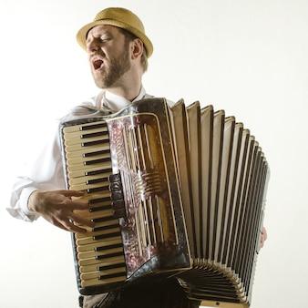 Ritratto di musicista professionista con fisarmonica a muro bianco
