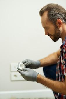 Ritratto di un elettricista riparatore professionista che indossa guanti protettivi durante l'installazione della presa a muro