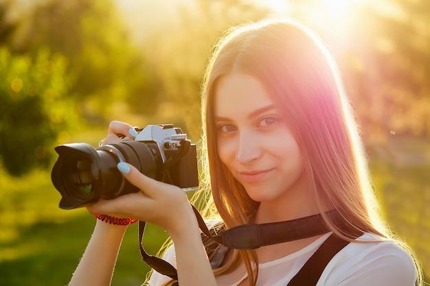 Ritratto del fotografo professionista della donna nel parco che fotografa su una macchina fotografica. servizio fotografico sessione fotografica in città