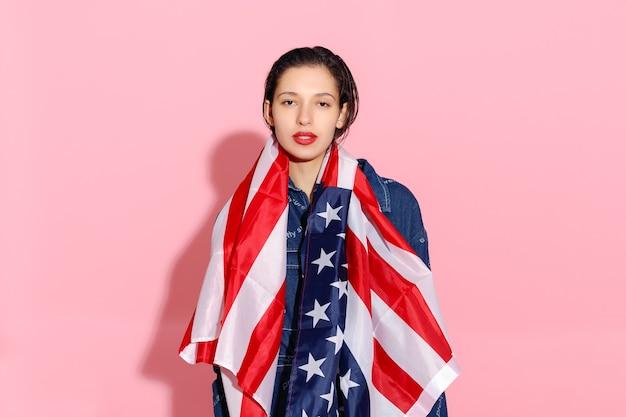 Ritratto di orgogliosa atleta femminile avvolto nella bandiera americana su sfondo rosa. giovane donna muscolare che guarda con sicurezza la macchina fotografica. protesta femminile per l'uguaglianza e l'emancipazione femminile