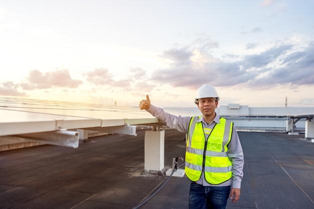 Il ritratto di un giovane ingegnere orgoglioso sorride soddisfatto del suo lavoro di successo su tetto, energie rinnovabili, tecnologia, elettricità, servizi, energia verde.