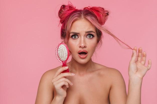 Ritratto di una giovane donna senza camicia perplessa che si tocca i capelli e tiene la spazzola